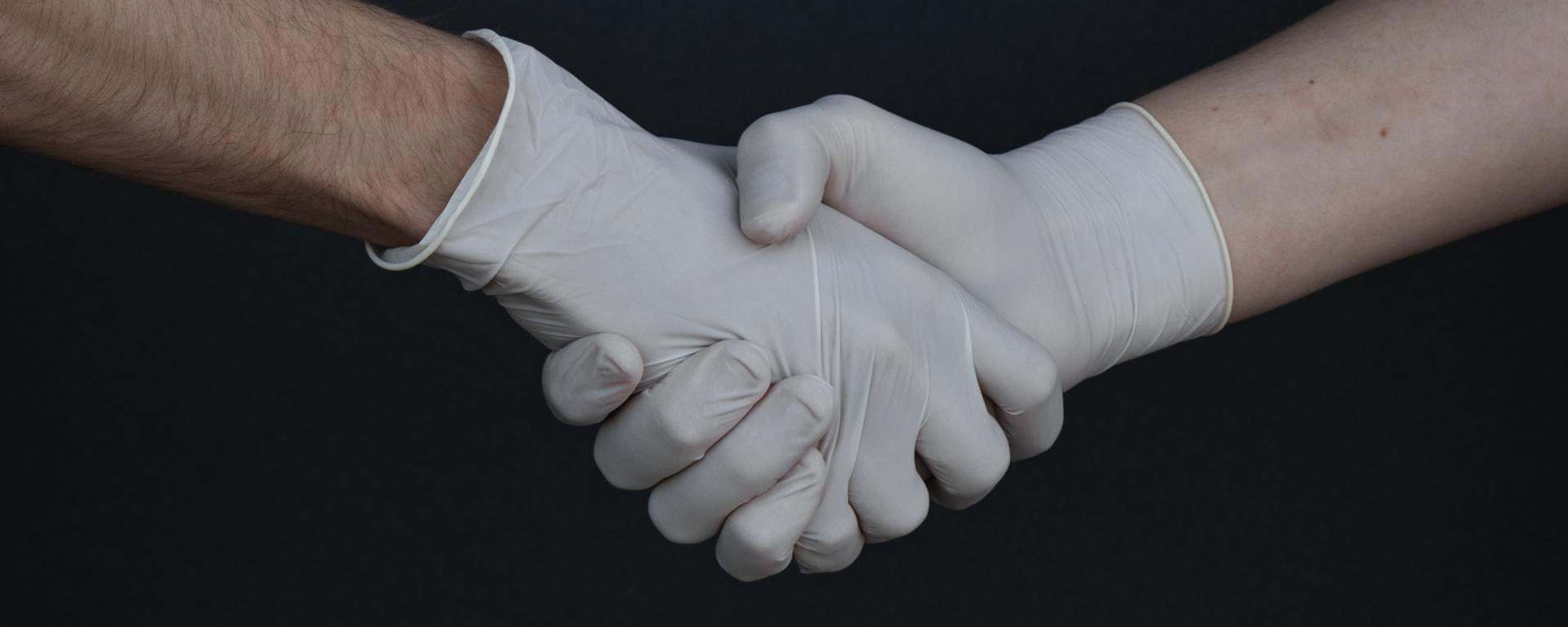 People Shaking Hands in Latex Gloves by Branimir Balogovic